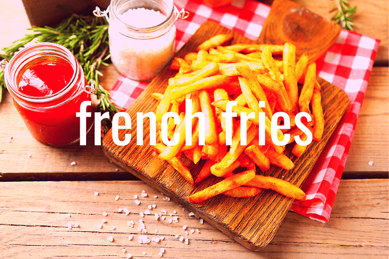 french fries on cutting board on checked tablecloth on wood table with condiments in jars on side