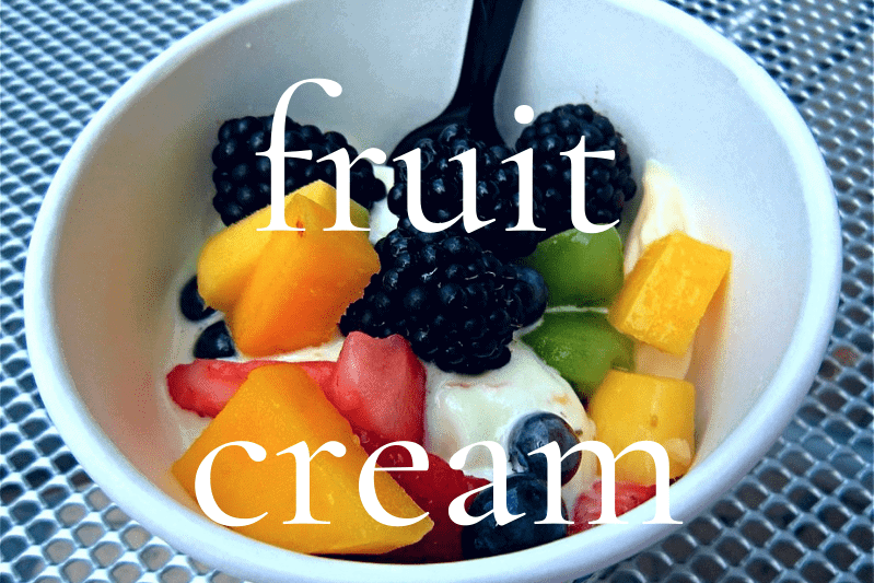 fruit and cream in small white bowl with spoon