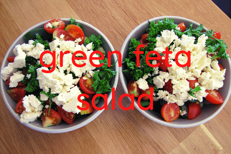 two bowls of green salad with feta on wooden table