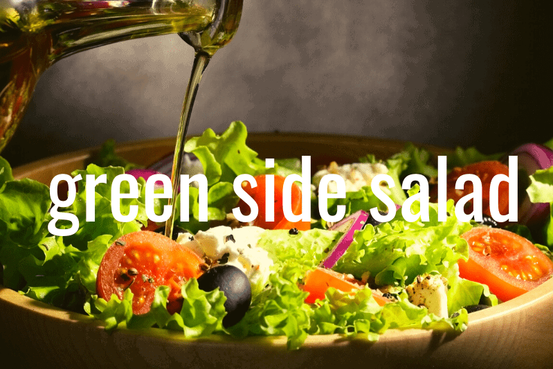 bottle of oil drizzling over green salad in wooden bowl with gray background