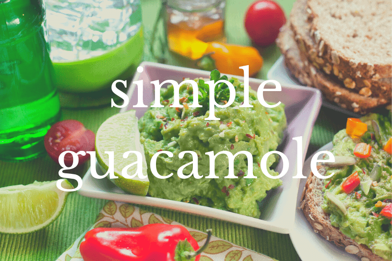 guacamole in square bowl surrounded by other food on table