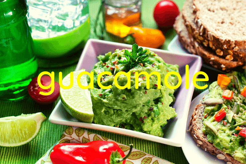 square white bowl of guacamole surrounded by other foods on dining room table