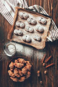 baked goods on tray with parchment paper covered in powdered sugar on towel on wooden table