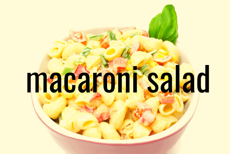 pink bowl of macaroni salad on white background