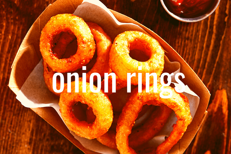 onion rings in basket on wooden table with metal ramekin of ketchup