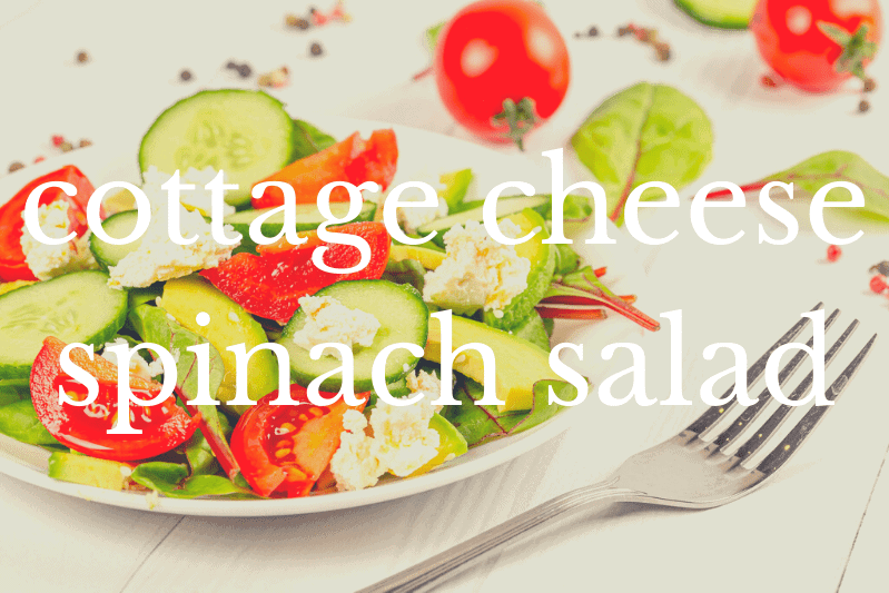 cottage cheese spinach salad in white bowl with fork on white tablecloth