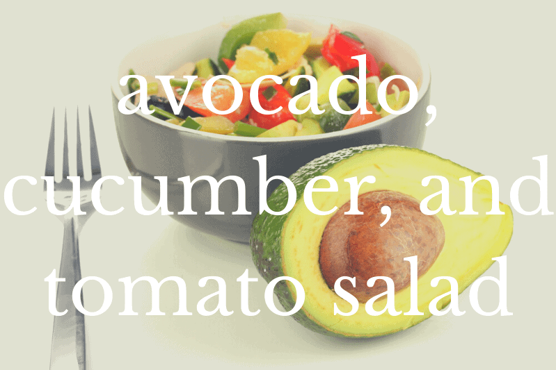 avocado, cucumber, and tomato salad in white bowl in front of half avocado on white table