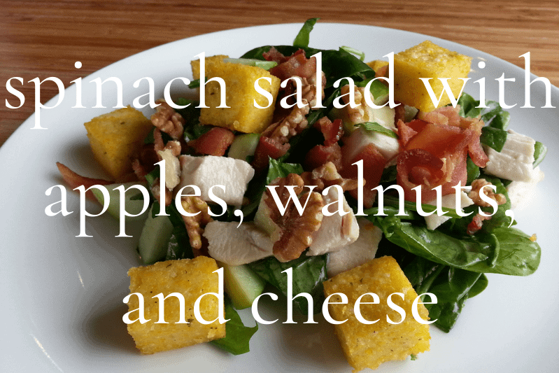 spinach salad with apples, walnuts, and cheese in white bowl
