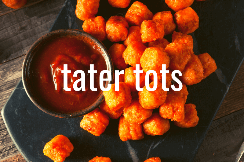 close up of tater tots with ketchup in metal ramekin