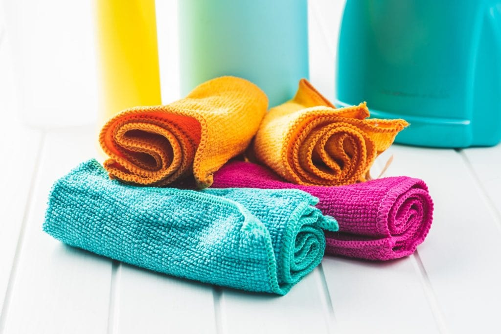 four colorful microfiber towels on white floor in front of containers