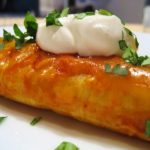 close up of enchilada with cilantro and sour cream