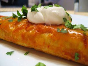 close up of enchilada with cilantro and sour cream