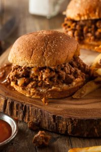 two sloppy joes on cutting board