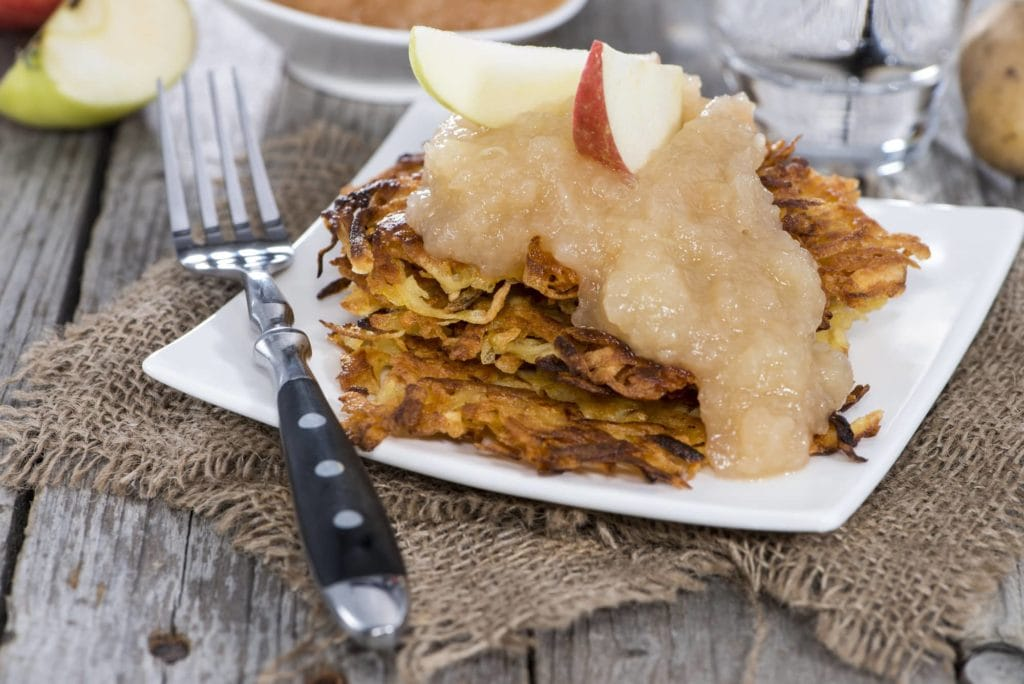 potato pancakes topped with applesauce on square white plate with fork on burlap place setting on wooden table