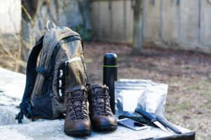 backpack, boots, thermos and knives with autumn leaves in background