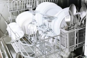 open dishwasher filled with clean glasses, silverware, and white dishes