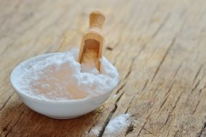 white bowl of baking soda with wooden scoop on wooden table
