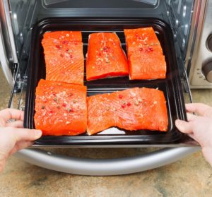 salmon on baking sheet being placed in convection oven