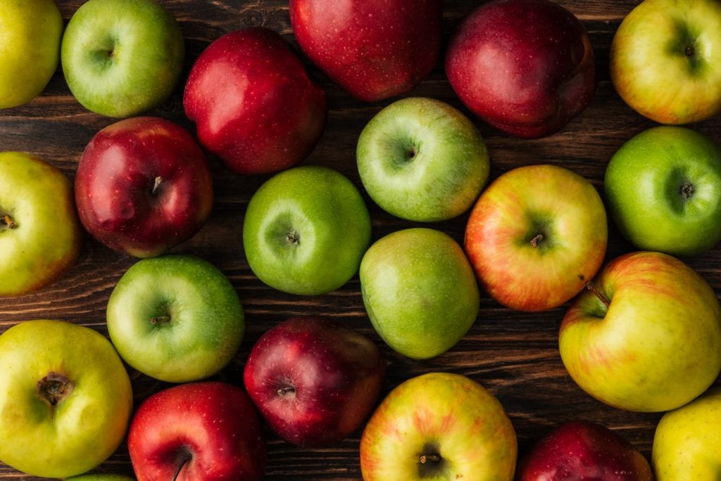 green and red apples on wooden table