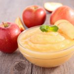 glass bowl of applesauce on wooden table with apples