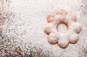 flower-shaped cookie on wooden table with powdered sugar sprinkled all around