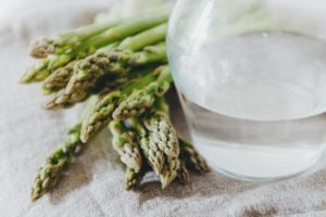 asparagus next to glass of water with a bit of water in bottom