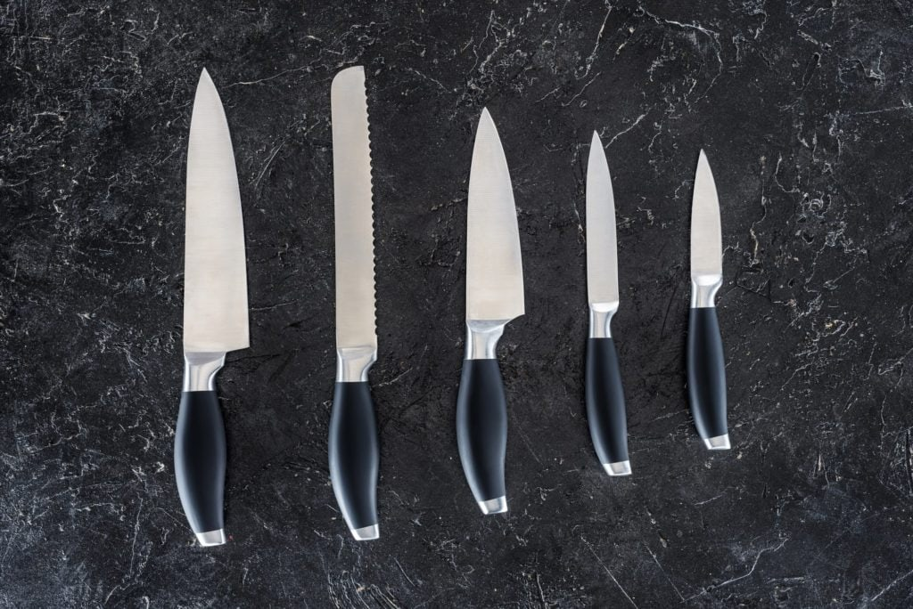 five knives lined up on black counter in order of sizes