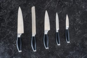 five knives lined up in order of size on black countertop
