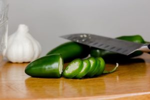 jalapeno sliced with knife on cutting board with garlic bulb in background