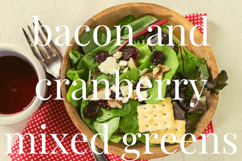cranberry and arugula salad in wood bowl on white table with fork and red napkin