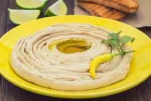 yellow bowl full of hummus