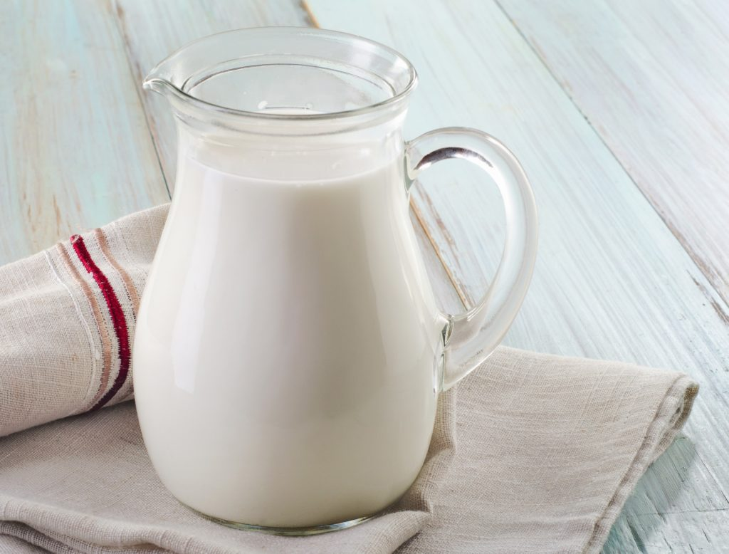 glass pitcher of milk on white wooden table with dishcloths