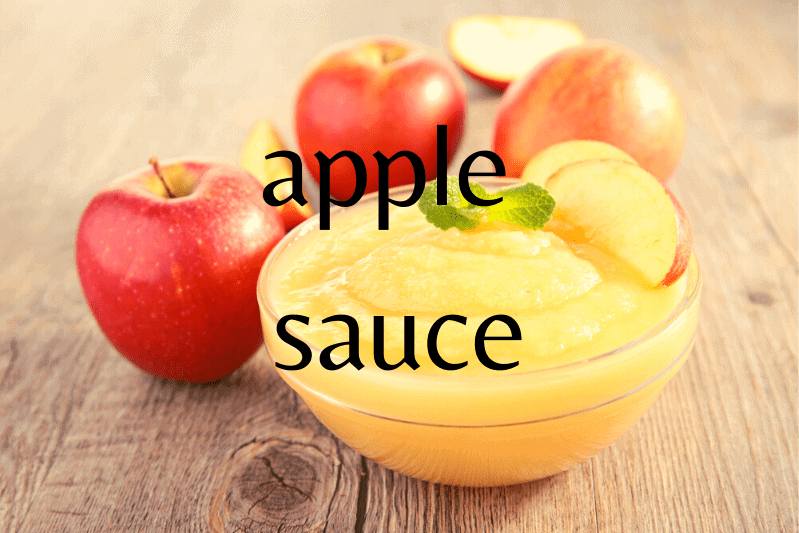 glass bowl of applesauce with apples on wood table