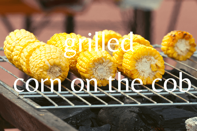 corn on the cob being grilled over charcoal grill