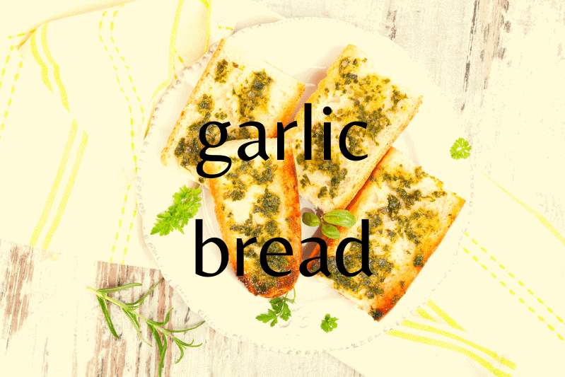 white plate on wooden table with four slices of garlic bread with parsley