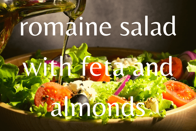 romaine salad with dressing being poured on it in wooden bowl
