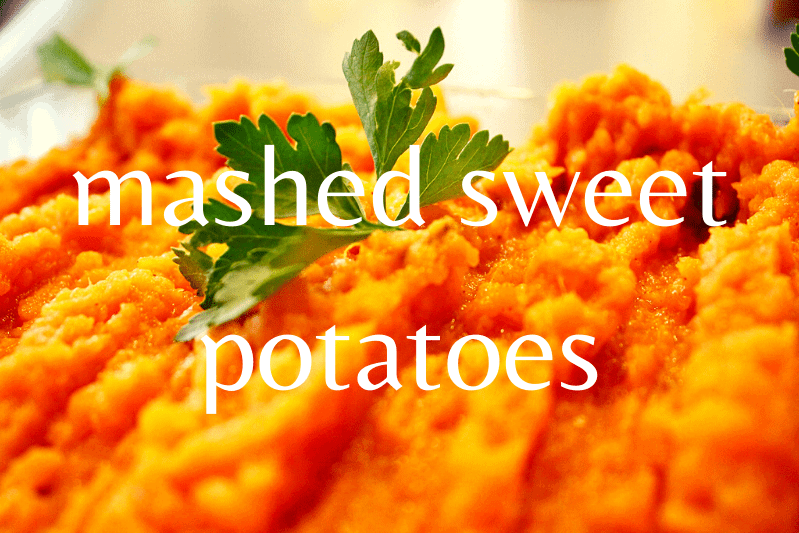 close up of mashed sweet potatoes with sprig of parsley on top