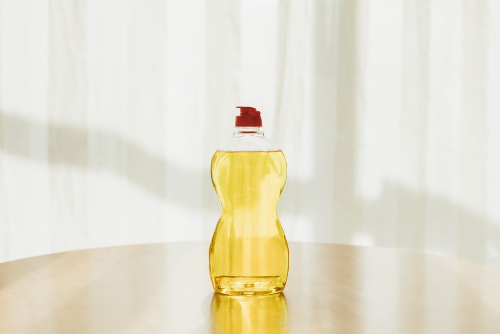 yellow dish soap in plastic bottle against white background