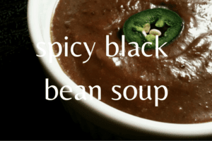 close up of black bean soup in white bowl with slice of jalapeno on top