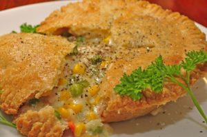 close up of chicken pot pie on white plate with parsley