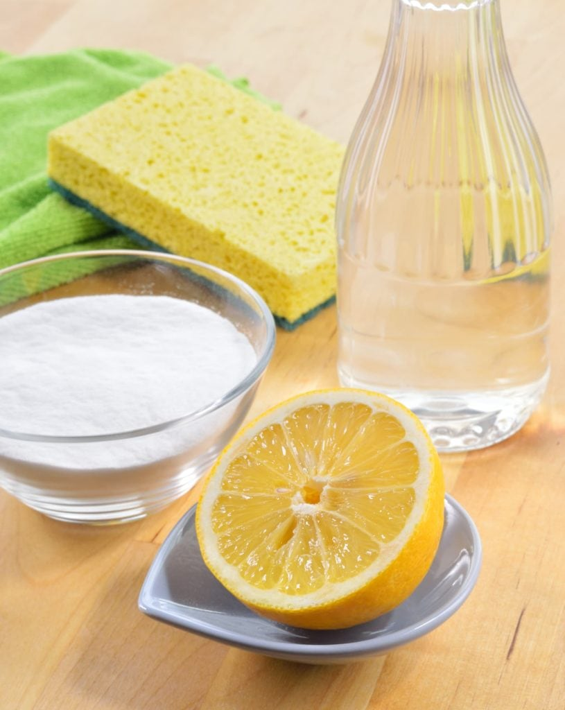 natural cleaning ingredients and sponges on wooden table