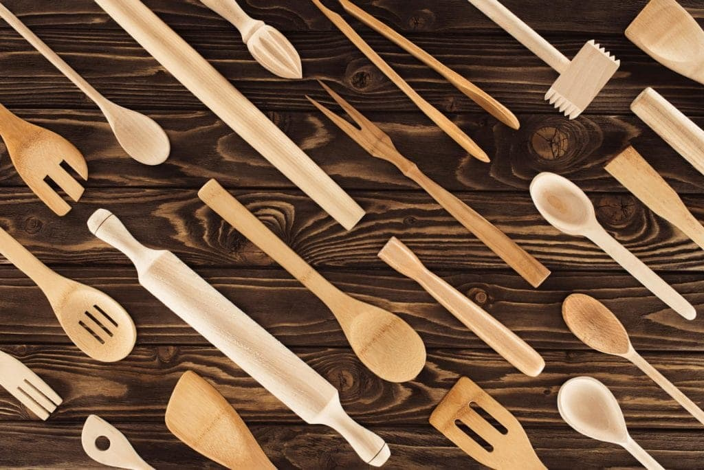 a number of wooden kitchen utensils lying on a dark wooden table