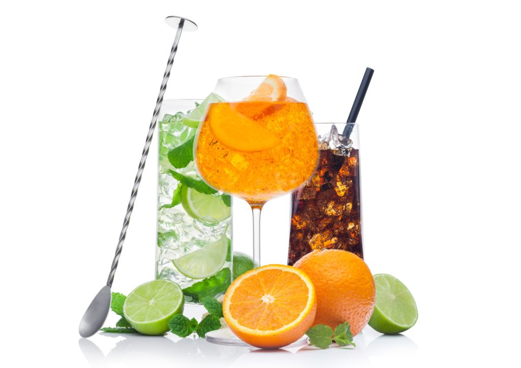 Glasses of Mojito, spritz and cuba libre summer alcoholic cocktail with ice cubes mint and lime on white background. with oranges and raw lime with steel bar spoon