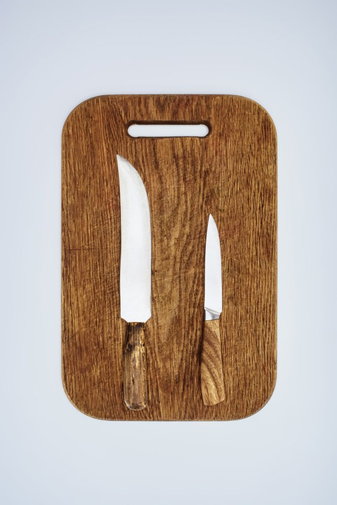 two wooden-handled knives on wooden cutting board on white background