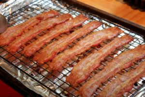 strips of bacon on wire rack over pan lined with aluminum foil